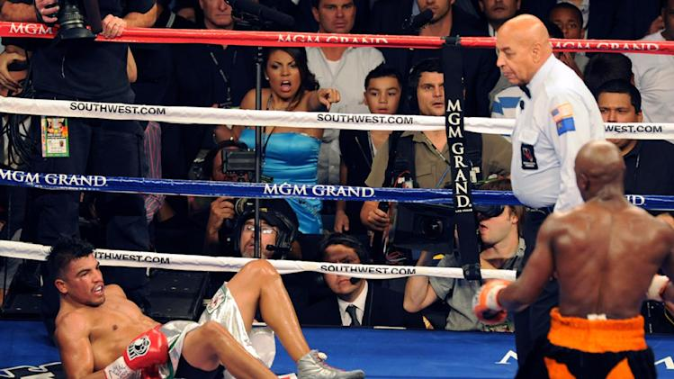 In this photo provided by the Las Vegas News Bureau, Floyd Mayweather knocks out Victor Ortiz as referee Joe Cortez watches during their WBC Welterweight bout, Saturday, Sept. 17, 2011, in Las Vegas. (AP Photo/Las Vegas News Bureau, Brian Jones)