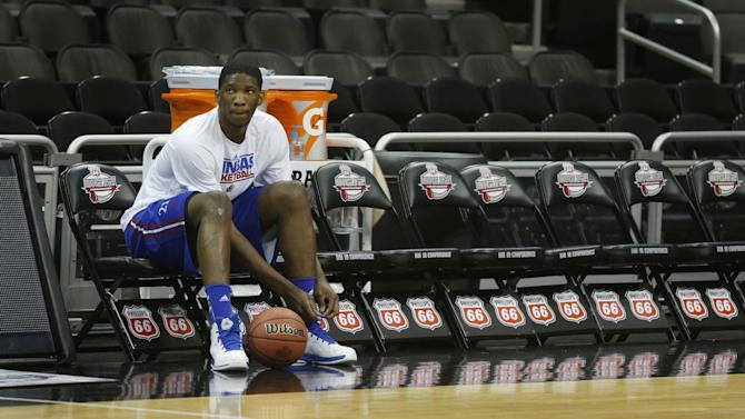 Kansas center Joel Embiid ties a shoe during practice for their opening NCAA basketball game in the Big 12 men's tournament in Kansas City, Mo., Wednesday, March 12, 2014. Kansas will play the winner of tonight's Texas Tech Oklahoma State game