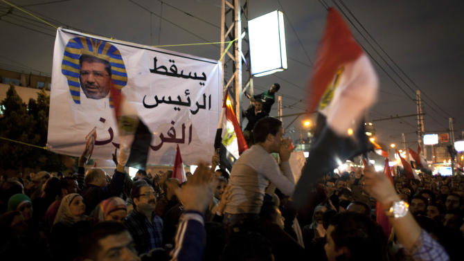 "Egyptian protesters carry national flags and chant anti Muslim Brotherhood slogans during a demonstration in front of the presidential palace in Cairo, Egypt, Tuesday, Dec. 4, 2012. A protest by tens of thousands of Egyptians outside the presidential palace in Cairo turned violent on Tuesday as tensions grew over Islamist President Mohammed Morsi's seizure of nearly unrestricted powers and a draft constitution hurriedly adopted by his allies. Arabic on the banner reads, ""down with the pharaoh president."" (AP Photo/Nasser Nasser)"