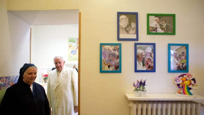 In this photo provided by the Vatican newspaper L'Osservatore Romano Pope Francis visits the Santa Marta dispensary at the Vatican, Saturday, Dec. 14, 2013. For more than 90 years, the dispensary on the Vatican grounds has been distributing milk, clothing, diapers, toys and even baby carriages to families in need. (AP Photo/L' Osservatore Romano, HO)