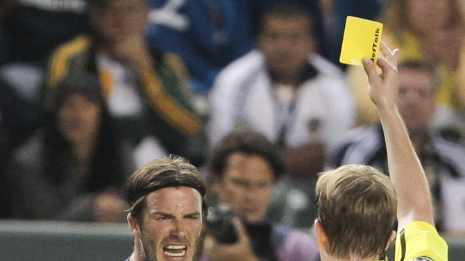 Los Angeles Galaxy midfielder David Beckham, left, reacts after receiving a yellow card during the second half of an MLS soccer match against the Columbus Crew, Wednesday, July 20, 2011, in Carson, Calif. The Galaxy won 1-0. (AP Photo/Bret Hartman)