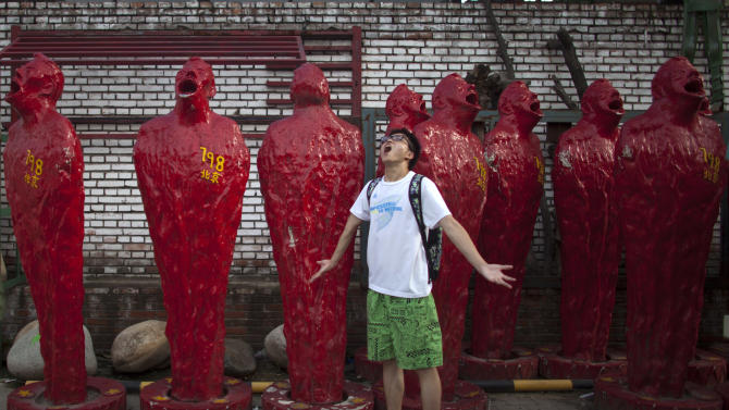 In this Thursday, July 12, 2012 photo, a man poses for photos in front of art pieces at the 798 Art District in Beijing, China. The city's art district, often compared to New York City's Greenwich Village, is a thriving community of about 400 galleries, shops and restaurants on the eastern edge of Beijing housed in a complex of former electronics factories built with the help of East Germany in the 1950s. (AP Photo/Alexander F. Yuan)