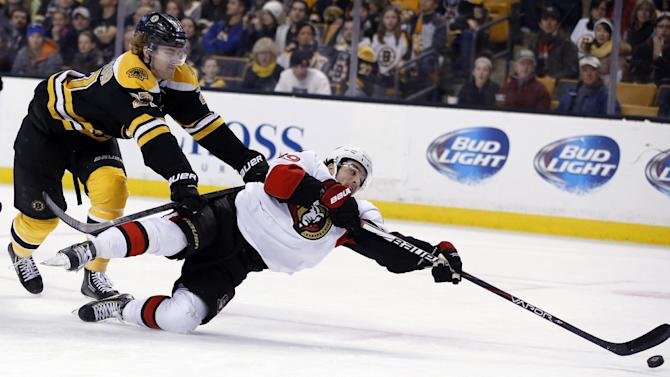 Boston Bruins defenseman Dougie Hamilton, left, tries to prevent Ottawa Senators left wing Cory Conacher (89) from shooting the puck during the third period of an NHL hockey game in Boston, Saturday, Feb. 8, 2014. The Bruins won 7-2