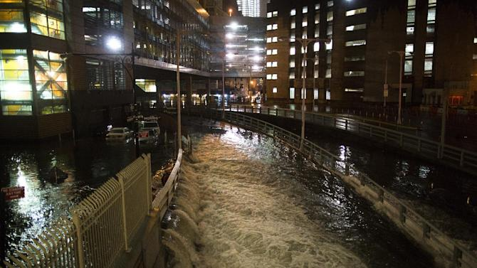 FILE - In this Oct. 29, 2012 file photo, sea water floods the entrance to the Brooklyn Battery Tunnel in New York during Superstorm Sandy.  A commission formed to examine ways to guard against storms like Sandy released a report Friday that calls for flood walls in subways, water pumps at airports and sea barriers along the coast. The final report was first obtained Tuesday, Jan. 8, 2013 by The Associated Press. The findings were officially released Friday, Jan. 11, 2013, by the office of Gov. Andrew Cuomo, who formed the commission.  (AP Photo/ John Minchillo, File)