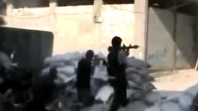 This image made from amateur video released by the Ugarit News and accessed Sunday, July 15, 2012, purports to show Free Syrian Army soldiers clashing with Syrian government forces in Damascus, Syria. Syrian troops and rebels clashed inside Damascus for a second day on Monday, causing plumes of black smoke to drift over the city's skyline in some of the worst violence in the tightly controlled capital since the country's crisis began 16 months ago. (AP Photo/Ugarit News via AP video) TV OUT, THE ASSOCIATED PRESS CANNOT INDEPENDENTLY VERIFY THE CONTENT, DATE, LOCATION OR AUTHENTICITY OF THIS MATERIAL