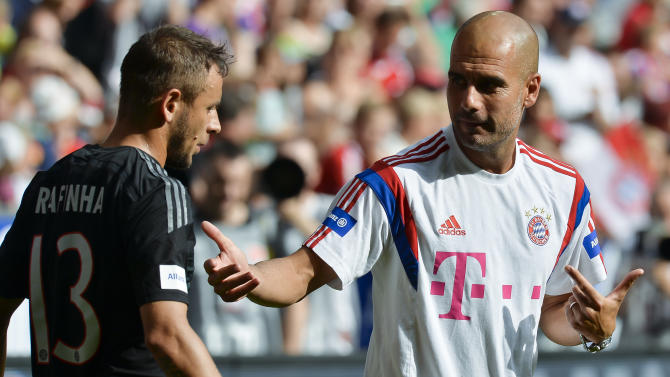 Bayern Munich's coach Pep Guardiola (R) talks to defender Rafa Rafinha (L) during training in Munich, southern Germany, on August 9, 2014