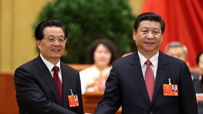 In this photo released by China's Xinhua News Agency, outgoing Chinese President Hu Jintao, left, poses with his successor Xi Jinping after Xi was elected to the presidency at a plenary meeting of the National People's Congress in Beijing Thursday, March 14, 2013. China's new leader Xi capped his rise Thursday by adding the largely ceremonial title of president, though he will need cautious maneuvering to consolidate his power and build support from a public that is increasingly clamoring for change. (AP Photo/Xinhua, Pang Xinglei) NO SALES