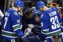 Vancouver Canucks' Jannik Hansen, center, of Denmark, is tended to by a trainer as Radim Vrbata, of the Czech Republic, and Henrik Sedin, right, of Sweden, watch after he was checked during the second period of an NHL hockey game against the Calgary Flames in Vancouver, British Columbia, on Saturday, Dec. 20, 2014. (AP Photo/The Canadian Press, Darryl Dyck)