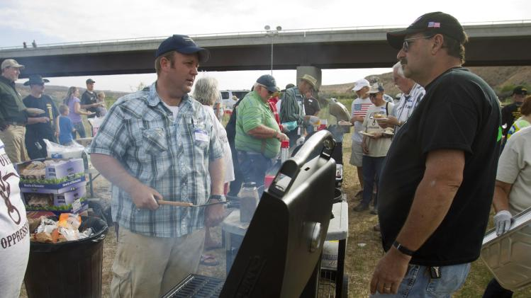 "Dave Bundy, son of rancher Cliven Bundy, talks with Larry Skaggs as he cooks hamburgers during a Bundy family ""Patriot Party"" near Bunkerville, Nevada"