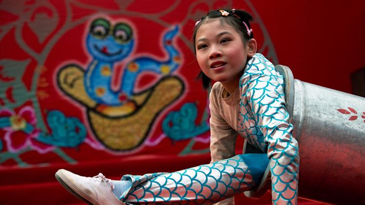 A Chinese girl uses a cylinder while performing an acrobatic show at the Dongyue Temple fair during the second day of the Chinese New Year in Beijing Monday, Feb. 11, 2013. Thousands attended temple fairs across the city to celebrate the arrival of the Year of the Snake. (AP Photo/Andy Wong)