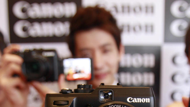 FILE - In this Jan. 10, 2012 file photo, a model poses with Canon's new digital camera Power Shot G1 X during its unveiling ceremony in Seoul, South Korea. Japan's Canon Inc. is moving toward fully automating digital camera production in an effort to cut costs. Jun Misumi, company spokesman, said Monday, May 21, the move to totally rely on robots and have no human workers will likely be completed in the next few years. He declined to give a date. (AP Photo/Lee Jin-man, File)
