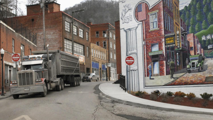 FILE - In this Feb. 9, 2011 file photo, a coal truck drives out of downtown Welch, W.Va. Rural places account for just 16 percent of the nation's population, the lowest share ever, while metro areas are booming into sprawling megalopolises.  (AP Photo/Jon C. Hancock, File)