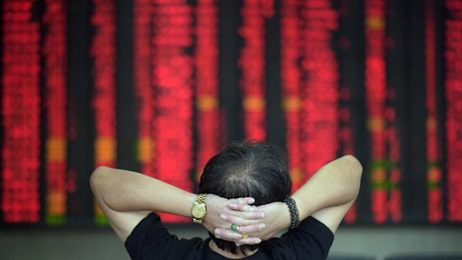 An investor sits in front of screens showing stock market movements at a brokerage house in Shanghai on July 29, 2015