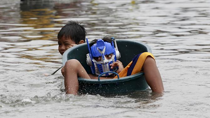 A boy tugs on a water basin with his friend wearing a mask as he wades through deep flooding caused by typhoon Linfa, locally named Egay, at Longos town in Malabon City