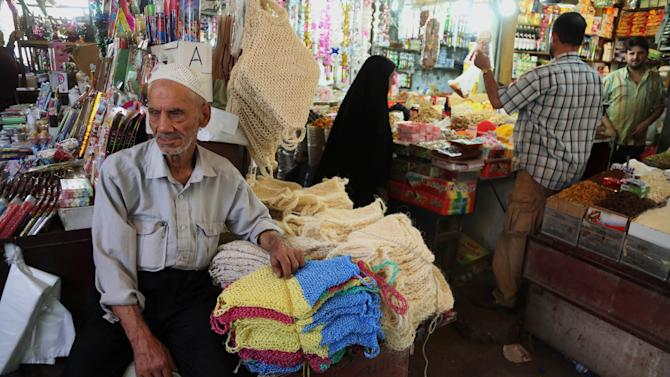 In this photo taken on June 17, 2014, people shop at a market in Baghdad, Iraq. While the Iraqi capital is not under any immediate threat of falling to the Sunni militants who have captured a wide swath of the country's north and west, battlefield setbacks and the conflict's growing sectarian slant is turning this city of 7 million into an anxiety-filled place waiting for disaster to happen. (AP Photo/Karim Kadim)