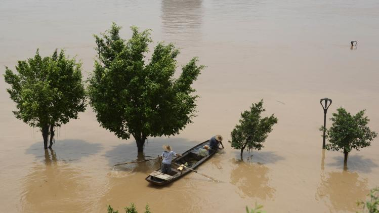 Residents on a boat catch fish near partially submerged trees flooded by an overflowing river after Typhoon Rammasun hit Nanning