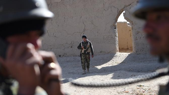 Afghan soldiers patrol the compound of the mosque where Mullah Omar founded the Taliban movement over 20 years ago, in the village of Sangesar