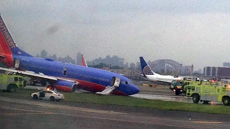 In this photo provided by Jared Rosenstein, a Southwest Airlines plane whose nose gear collapsed as it touched down on the runway is surrounded by emergency vehicles at LaGuardia Airport in New York on Monday, July 22, 2013. The plane was carrying 149 passengers and crew. (AP Photo/Jared Rosenstein) MANDATORY CREDIT