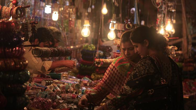 Women check glass bangles from a stall as they shop in a market place ahead of Eid al-Fitr celebrations in Islamabad