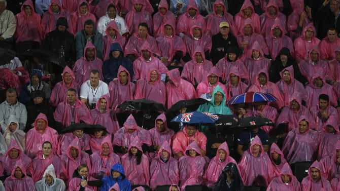 Spectators shelter from the rain as they watch the women's beach volleyball semifinal match between Ross and Kessy of the U.S. and Brazil's Juliana and Larissa at Horse Guards Parade during the London 2012 Olympic Games