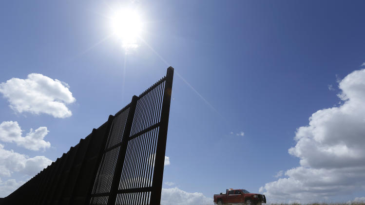 FILE - In this Sept. 6, 2012 file photo, cotton farmer Teofilo Flores drives his truck along the U.S.-Mexico border fence that passes through his property in Brownsville, Texas. The fence along this section of the border divided people from swaths of their own land, but also struck many as an offensive gesture in this bicultural, bilingual region. (AP Photo/Eric Gay)