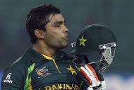 Pakistan's Umar Akmal kisses his helmet after scoring a century during the Asia Cup one-day international cricket tournament against Afghanistan in Fatullah, near Dhaka, Bangladesh, Thursday, Feb. 27, 2014. (AP Photo/A.M. Ahad)