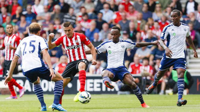 Southampton's Dusan Tadic fails to score while under pressure from West Bromwich Albion's Craig Dawson, left,, Saido Berahino and Andre Wisdom, right, during the English Premier League match at St Mary's, Southampton, England, Saturday Aug. 23, 2014. (AP Photo/PA, Chris Ison) UNITED KINGDOM OUT NO SALES NO ARCHIVE