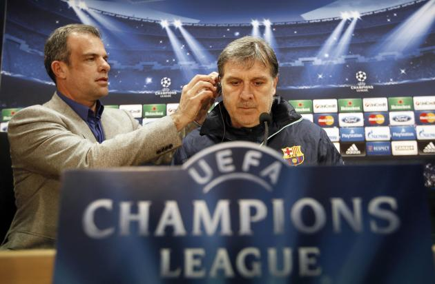Barcelona's press officer Teres sets a translation device on coach Martino before a news conference at Ciutat Esportiva Joan Gamper in Sant Joan Despi in Barcelona