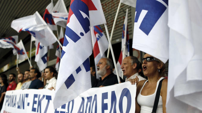 Communist-backed unionists hold a banner and chant slogans, as they block access to the ministry building in Athens, on Tuesday, Sept. 11, 2012.  The banners reads '' Troika, IMF ICB get out''.  The protest came ahead of a visit there by debt inspectors monitoring Greece's austerity program. (AP Photo/Petros Giannakouris)