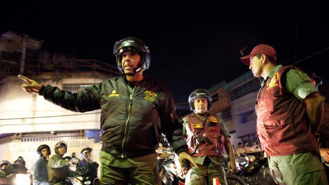 """In this May 14, 2013 photo, Gen. Antonio Benavides, left, gives instructions to a soldiers during a security operation that is part of the """"Secure Homeland"""" initiative in Petare, one of the most dangerous neighborhoods of Caracas, Venezuela.  The murder rate doubled during the 14-year-rule of the late President Hugo Chavez as cheap access to guns and an ineffective justice system fed a culture of violence in slums like Petare, parts of which have become no-go zones for outsiders, including police. (AP Photo/Ariana Cubillos)"""