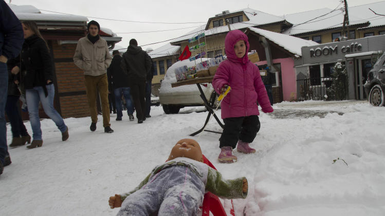 A child pulls her doll on a snow sledge in the Kosovo capital, Pristina, Tuesday, Dec. 11, 2012. Weather forecasts predict cold temperatures and snow for Eastern Europe during the upcoming days. (AP Photo/Visar Kryeziu )