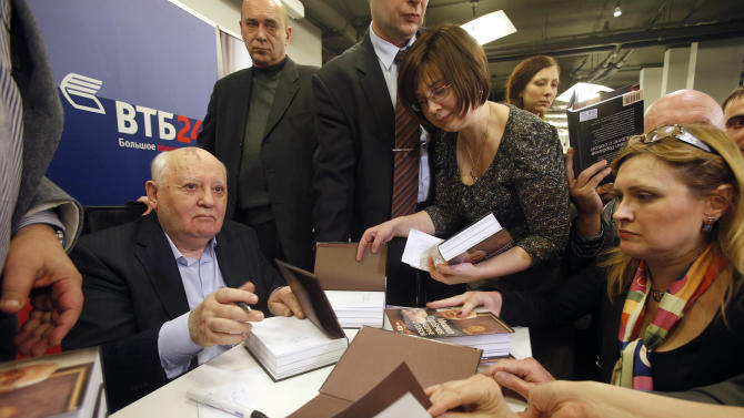 Former Soviet leader Mikhail Gorbachev, left, signs his book in a book shop in Moscow, Russia, Tuesday, Nov. 13, 2012. Mikhail Gorbachev looks back at his life in his new book Alone with Myself. He talks about his young years with a remarkable candor in the book, which is full of love for his late wife.  (AP Photo/Misha Japaridze)