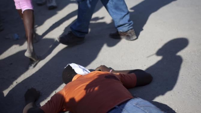 In this picture taken Feb. 29, 2012, the body of a motorcycle rider lies on the ground after being killed by a robber as the shadows of onlookers are projected on the body in Port-au-Prince, Haiti. Haiti has seen a dramatic increase in violent crimes in the shanties of the Caribbean nation's major cities and Haitians have lost faith in their police force over the past six months, according to a study authored by social scientists Athena Kolbe and Robert Muggah released on Sunday, March 4, 2012. (AP Photo/Ramon Espinosa)