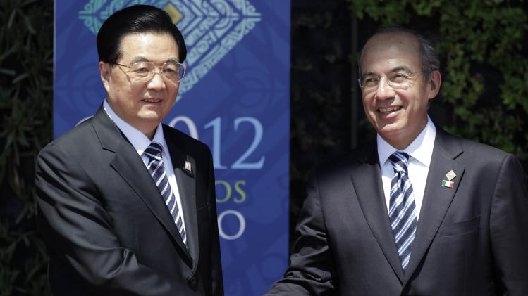 China's President Hu Jintao, left, greets Mexico's President Felipe Calderon during the opening ceremony of the G20 Summit in Los Cabos, Mexico, Monday, June 18, 2012. (AP Photo/Eduardo Verdugo)