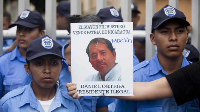 """A demonstrator holds out a picture of Nicaragua's President Daniel Ortega that reads in Spanish """"The biggest thief and traitor of Nicaragua, Daniel Ortega illegal President"""" in front of a line of police during a protest against a canal project outside the National Assembly in Managua, Nicaragua, Thursday, June 13, 2013. A multi-billion dollar proposal to plow a massive rival to the Panama Canal across the middle of Nicaragua was approved by the National Assembly Thursday, capping a lightning-fast approval process that has provoked deep skepticism among shipping experts and concern among environmentalists. (AP Photo/Esteban Felix)"""