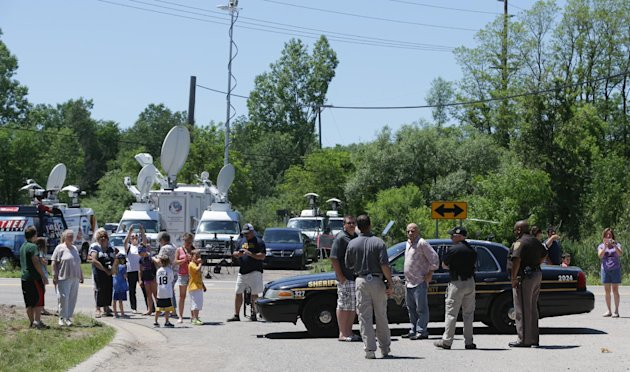 Curious neighbors gather as law enforcement local authorities search for Jimmy Hoffa's body in a field in Oakland Township, Monday, June 17, 2013. Hoffa disappeared from a Detroit-area restaurant in 1