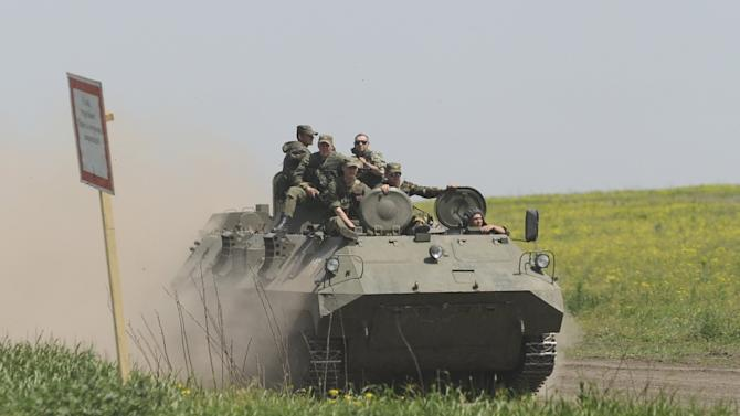Men wearing military uniforms ride atop APC during training session at Kuzminsky military training ground in Rostov region