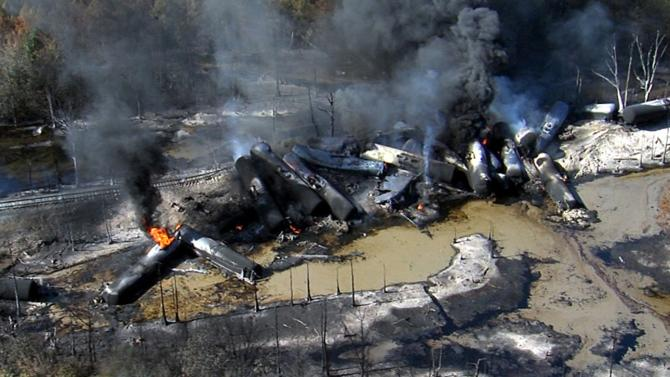 Smoke rises from a number of cars that derailed and exploded from a train carrying crude oil in Aliceville
