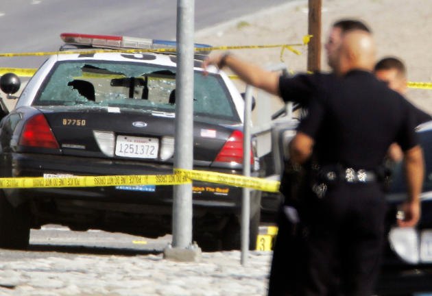 Police tape surrounds a bullet-damaged Los Angeles Police vehicle on Thursday Feb. 7, 2013 in Corona, Calif.  Former Los Angeles police officer Christopher Dorner is suspected if shooting at the two L