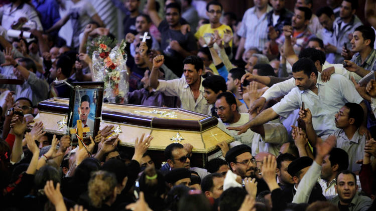 Egyptian Christians carry the coffin of Morqos Kamal, at the Saint Mark Coptic cathedral in Cairo, Egypt, Sunday, April 7, 2013. Several Egyptians including 4 Christians and a Muslim were killed in sectarian clashes before dawn in Qalubiya, just outside of Cairo on Saturday, April 6, 2013. (AP Photo/Amr Nabil)