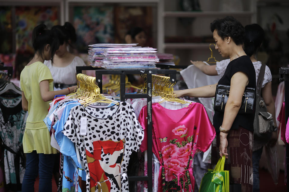 Customers look at displays of silk dress at a shop, Wednesday June 13, 2012 in Shanghai, China. Chinese consumers can afford to splash out more on higher quality products, but also expect better value for money than in the past, according to a study by the American Chamber of Commerce. (AP Photo/Eugene Hoshiko)