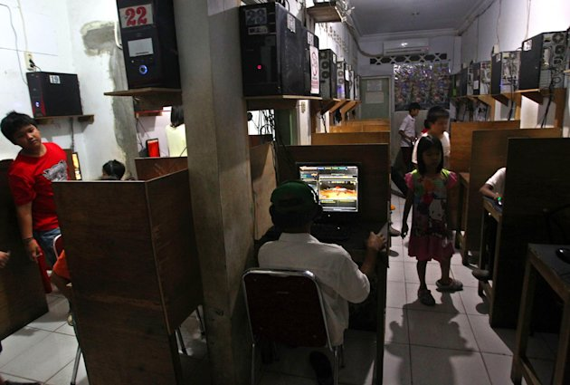 In this June 19, 2013 photo, Indonesian children surf the net at and play games an internet cafe in Jakarta, Indonesia. The use of social networking to groom potential attackers is posing a new challe