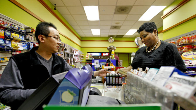 "Benita Lewis, 41, of Atlanta, right, buys a Powerball lottery ticket from store worker Bryant Kim, at a convenience store, Wednesday, Nov. 28, 2012, in Atlanta. ""I did feel nervous buying it like I could be the one,"" says Lewis. ""I'm going to retire and pay off all my family's debt, immediate family, I got to that back, immediate family's debt."" (AP Photo/David Goldman)"