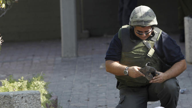 An Israeli police sapper collects the remains of a rocket fired by Palestinian militants from the Gaza Strip that landed in the southern Israeli town of Ashkelon, Monday, Nov. 19, 2012. Exchange of fire between Israel and Gaza militants continued for the sixth day on Monday. (AP Photo/Tsafrir Abayov)