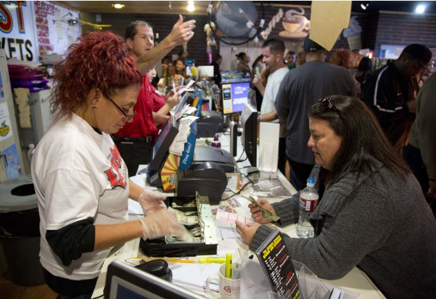 Arizona Last Stop shop employees sell Powerball tickets to customers who waited in line for more than an hour, Tuesday, Nov. 27, 2012, in White Hills, Ariz. There has been no Powerball winner since Oc