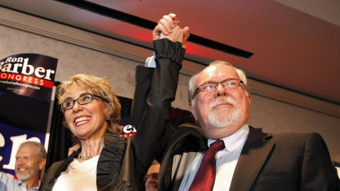 FILE - In a Tuesday, June 12, 2012 file photo, in an election to fill former Rep. Gabrielle Giffords, left, D-Ariz., congressional seat, Democratic candidate Ron Barber, right, celebrates a victory with Giffords and supporters at a post election event, in Tucson, Ariz. Giffords and her husband on Tuesday, Jan. 8, 2014 launched a political action committee aimed at curbing gun violence as Tucson residents paused to mark the anniversary of the shooting rampage there. (AP Photo/Ross D. Franklin, File)