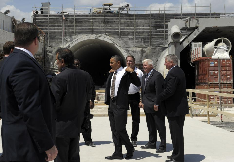 President Barack Obama removes his jacket before touring a tunnel project at the Port of Miami, Friday, March 29, 2013, while promoting a plan to create jobs by attracting private investment in highways and other public works. (AP Photo/Susan Walsh)