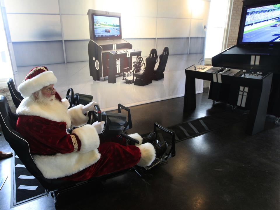 Santa Clause, portrayed by Brady White, plays on the custom made Pinel & Pinel Arcade PS Trunk system during the unveiling of the Neiman Marcus 2012 Christmas Book in Dallas, Tuesday, Oct. 9, 2012. The fantasy gift arcade is priced for sale at $90,000.  (AP Photo/LM Otero)