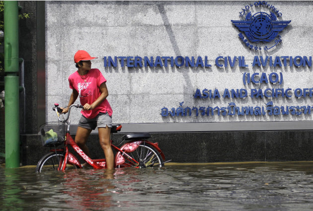 A Thai resident checks her surroundings as she tries to cross the floods on a bicycle at the Lad Phrao district in Bangkok, Thailand, Saturday, Nov. 5, 2011. Thailand's record floods continued to cree