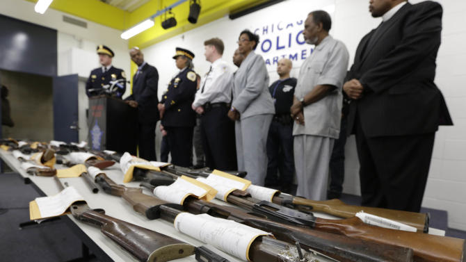 Chicago Police First Deputy Superintendent Alfonsa Wysinger, second from left, accompanied by Deputy Chief Wayne Gulliford, left, speaks at a news conference Monday, Jan. 28, 2013, in Chicago. The pair joined other officers, elected officials, clergy, and community members, with a display of recently recovered firearms from the 574 seized to date beginning Jan. 1, 2013. (AP Photo/M. Spencer Green)